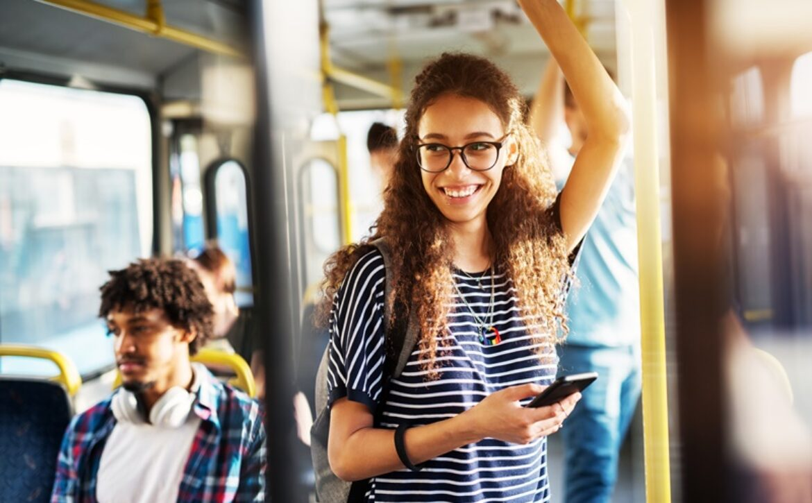 Young gorgeous cheerful woman is standing on the bus using the phone and smiling.